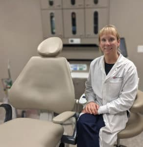 Heather Luebben pictured next to a dental chair