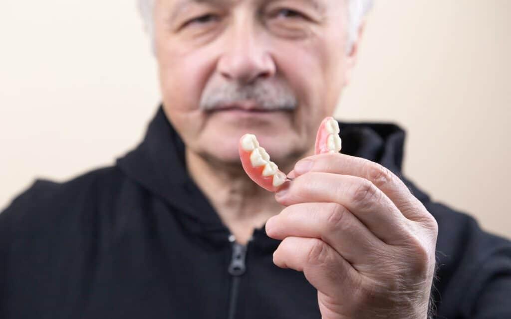 man holds denture